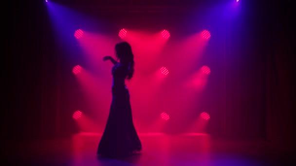 Silhouette Mädchen in einem orientalischen Kostüm führt klassischen Bauchtanz auf. Gedreht in einem dunklen Studio mit Rauch und roter Neonbeleuchtung.