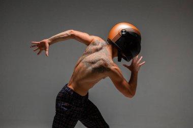 Handsome guy racer in helmet runs on grey background in studio. Kart racing school poster. Body with tattoo