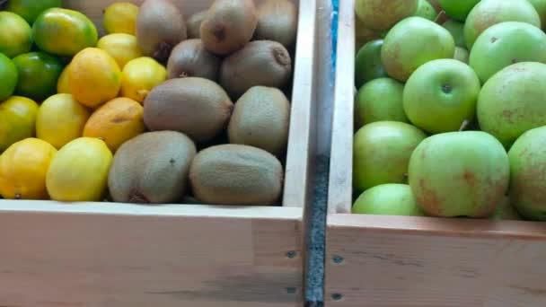 panoramatické zblízka střílel dřevěných beden s ovoce - pomeranče, kiwi, ananas, jablka, hrušky, mrkev