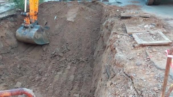 excavator ladle scoop bucket digging a pit at construction site. close up handheld shot