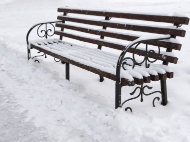 closeup of cute wooden bench at park at winter covered with snow. outdoor winter park image