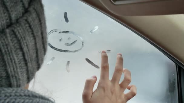 Teenage girl in wool hat and scarf drawing sun on foggy frowned car window  at winter season  4k video footage  miss for summer concept