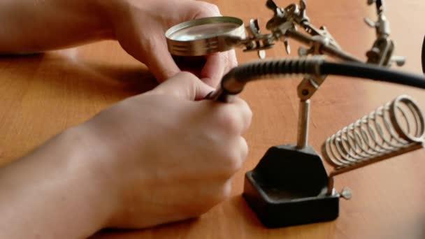 uzavření rukou technika dělá na psacím stole nějaké opravy nebo řemeslo s zvětšovací sklenicí a otočným nástrojem nebo železem. Home Úvod koncepce vylepšení 4k video záběr