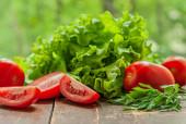 čerstvý křupavý salát a šťavnatá zralá švestková rajčata na dřevěném stole u okna zavřít