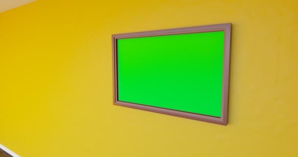 Fotografický rám visí na dřevěné stěně, vodorovně. Sledování.
