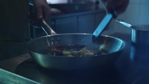 Der Koch in der Schmiede des Restaurants Pommes frites, mischt eine Pfanne mit Meeresfrüchten