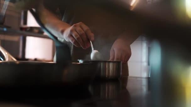 Pracovní atmosféra v kuchyni restaurace. Šéfkuchaři připravují jídlo..