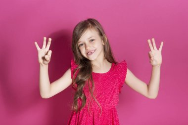 Little 8 years old girl make some emotional gesture with her hands on a pink neutral background. She has long brunette hair and wear red summer dress. Funny expression on her face