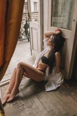 Sexy fit brunette woman in underwear in luxury retro interior at home.