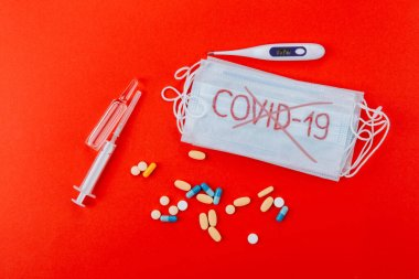 Protective medical mask with the inscription Covid-19, syringes, thermometer, ampoules and medicines on a red background. The word COVID-19 is crossed out.