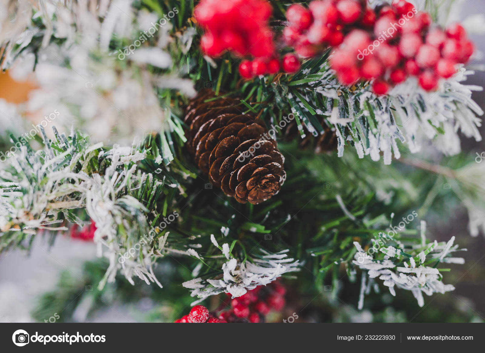 Detail of small Christmas tree with snow mistletoe and pine cone decorations cozy festive winter holidays feeling