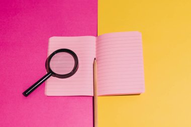 magnifying glass on notebook with blank pink pages on contrastin