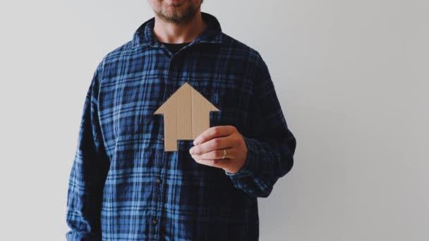 mladí lidé a trhu s nemovitostmi muž s hipster flanelové košile drží dům ikony a dělat palce nahoru znamení