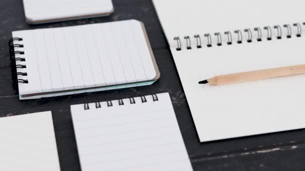 egy új projekt koncepcionális csendélet csoport különböző jegyzettömbök és jegyzetfüzetek nyílt az asztalon üres oldalak fényképezőgép panning körül a jelenetet