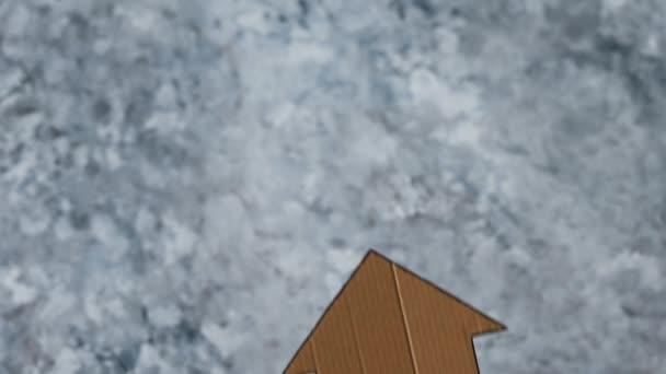 Immobilieninvestition oder Versicherungskonzept, Häusersymbol in der Hand halten und aus dem Rahmen fallen