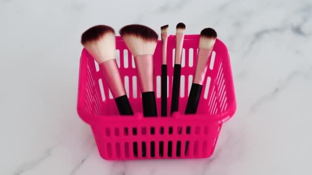 kosmetický průmysl a základní produkty koncept, růžový nákupní košík s různými make-up štětci v něm pro obličej a oční make-up a fotoaparát rozostření