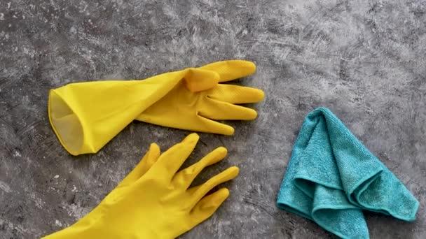 Desinfektion und Reinigung gegen Bakterien und Viren, gelbe Putzhandschuhe und Mikrofasertuch auf der zu sanierenden Oberfläche und Kameraschwenk senkrecht