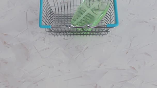 hygiena proti virům a bakteriím koncept, ruka dezinfekční láhev uvnitř nákupního košíku symbol vysoce vyhledávané produkty v dobách sebeizolace a karantény s kamerou panting vertikálně
