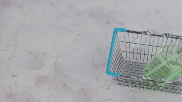 higiénia a vírusok és baktériumok ellen, kézfertőtlenítő palack a bevásárlókosár szimbólumában nagyon keresett termékek az önizolálás és a karantén idején, valamint a fényképezőgép vízszintes pásztázása
