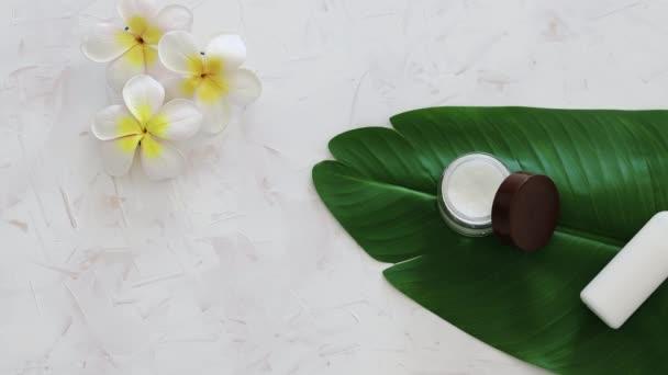 vegán természetes szépség nélkül durva kémiai fogalom, pot arckrém és üveg testápoló trópusi zöld levél monoi virágok és fényképezőgép panning vízszintesen