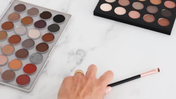 kosmetický průmysl a make-up produkty koncepční zátiší, oční palety s nahotou a bronzovými tóny a ruční umisťování štětců vedle nich na mramorový stůl
