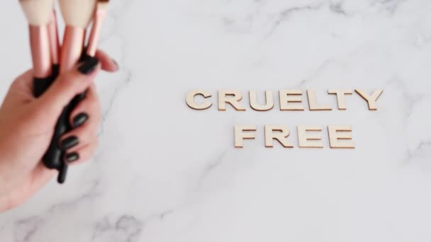 beauty industry and vegan products conceptual still-life, hand holding make-up brushes with Cruelty free text next to them referring to the use of synthetic bristle