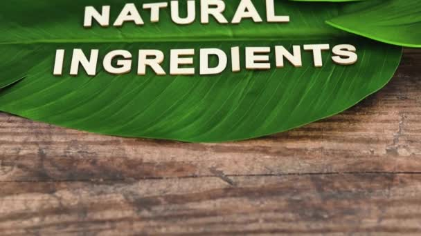 beauty industry and ethical vegan products conceptual still-life, Natural Ingredients message on tropical banana leaf with camera panning vertically