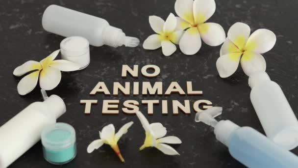 krutost-free kosmetické výrobky konceptuální zátiší, No Animal Testing zpráva mezi krémy a kosmetických prostředků na černém mramorovém stole a fotoaparátu rozostření pomalu