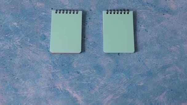 üzleti szervezés és tervezési koncepció, pár megfelelő kék jegyzetfüzet kék háttérrel és kamera dönthető