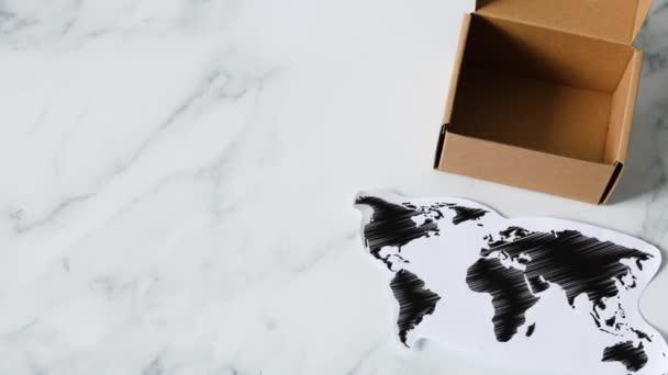 celosvětové dodávky, miniaturní poštovní balíček vedle mapy světa a kamerového pásu