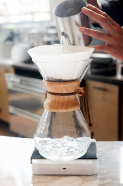 Barista pouring hot water over roasted grinded coffee powder making drip brew coffee