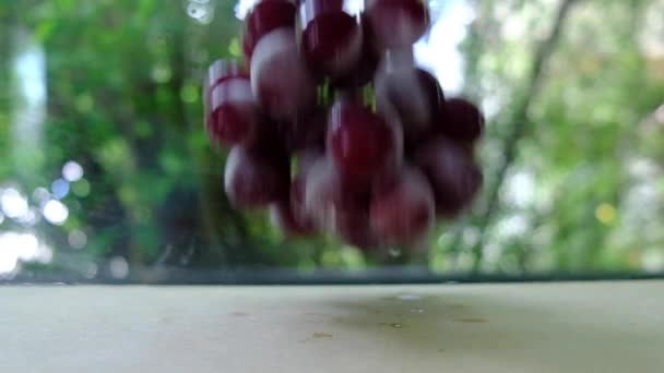 Slow motion video of red grapes drop on wood table