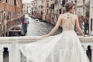 Beautiful bride with tattoo on back, dressed in elegant, luxury ivory dress and updo hairstyle, posing on a bridge over the canal in Venice stock vector
