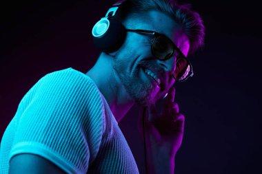 Neon light portrait of bearded smiling man in headphones, sunglasses, white t-shirt. Listening to music