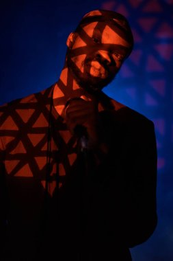 dark-skinned handsome guy in a bandana, black classic jacket and t-shirt holding a microphone in his hand,standing in the shadow  on a blue light background and looking at the camera