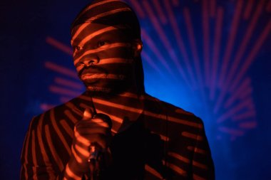 dark-skinned handsome guy in a bandana, black classic jacket and t-shirt holding a microphone in his hand,standing in the shadow on a blue light background and looking away