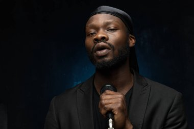 dark-skinned handsome guy in a bandana, black classic jacket and t-shirt holds a microphone in his hand, looks in the camera and singing
