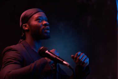 dark-skinned handsome guy in a bandana, black classic jacket and t-shirt holds a microphone in his hands and emotionally sings in a dark studio with red light