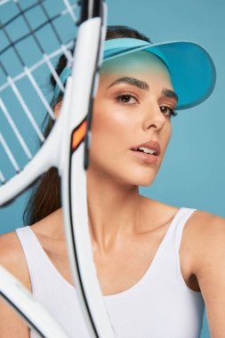 portrait photo of a beautiful sporty girl in white top and blue tennis cap, posing with a racket on a blue background