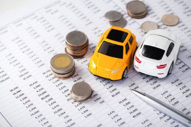 Cars with coins on financial statement