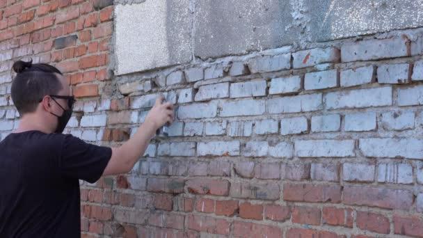 vandál fekete maszk és szemüveg festi a falat spray festék egy nyári napon