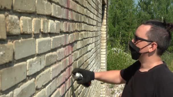 fiatal férfi fekete maszk és szemüveg festi a falat spray festék egy nyári napon