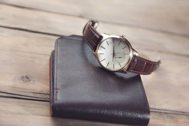 elegant watch and wallet on wooden table