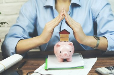woman with  home or house model and piggy bank