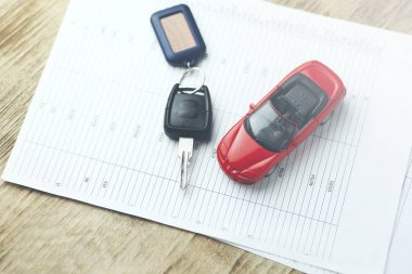 car model and auto key on documents on table