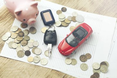 car model and auto key with money on documents on table