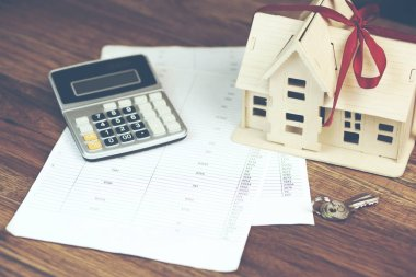 house model with calculator and key on documents over wooden background