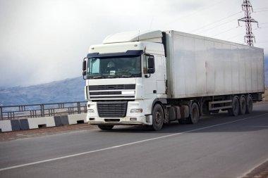 Rural landscape with an asphalt highway and  truck
