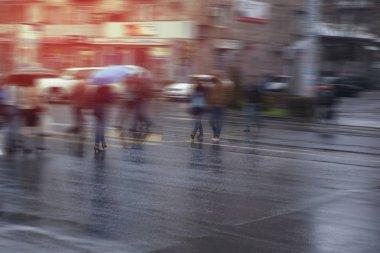 people walking in  rush hour in the rain