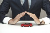 mans  hands over  small red car on table